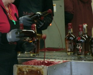 "4 workers dip the red wax tops on the ""46"" bottles"