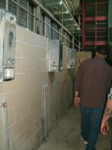 "Shower ""hall"" below three stories of overlooking cells. regular inmate cell block moundvills state Penitentuary"