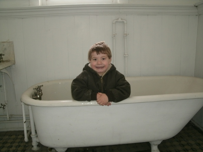 Christopher sitting the bath tube of the Lewis Bennett Library of Weston West Virginia