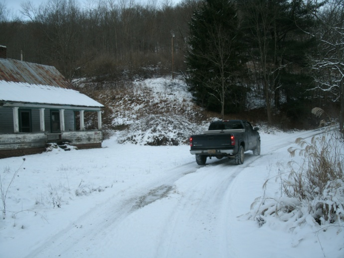 toms truck on a snowy road near old house