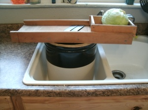 cabbage sitting on top of kraut cutter and crock