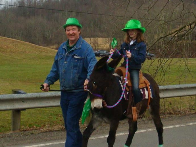 Jerry Posey leading his grand daughter in the St Patrick's day celebration in Ireland, West Virginia on her Donkey Heidi