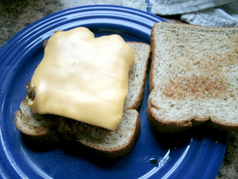 Giovanni sandwich with out peppers, bread, hamburger patty, american cheese.