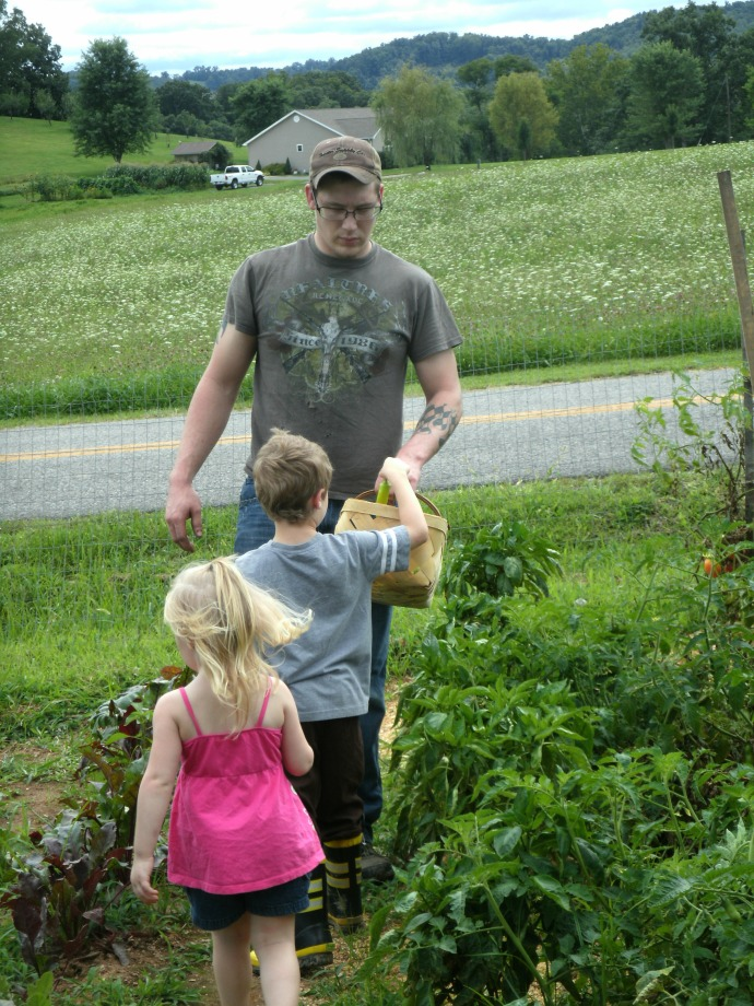 Cody, Christopher and Paige Powers picking tomatoes and peppers in the garden