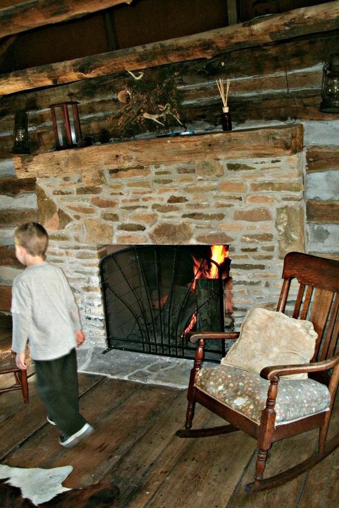 Christopher walking in front of fire place  in cabin at Spiker farm