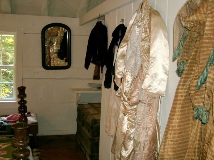 vintage clothing hung on back wall of cabin