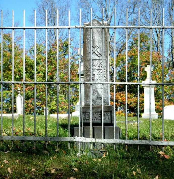 Headstone of john Kennedy through iron fence