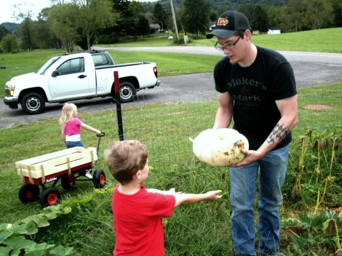Christopher and Cody picking pumpkins and Paige on the way with the wagon