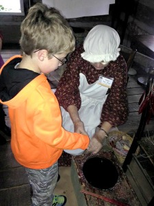 Christopher dipping candles at Fort New Salem, Salem West Virginia
