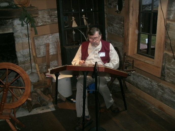 Man playing a hammer Dulcimer at Fort New Salem