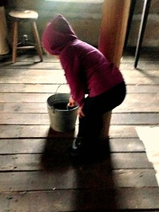 Paige dipping her candle in a bucket of cold water before adding another coat of wax at Fort New Salem, Salem West Virginia