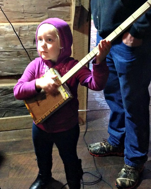 Paige playing the cigar box banjo