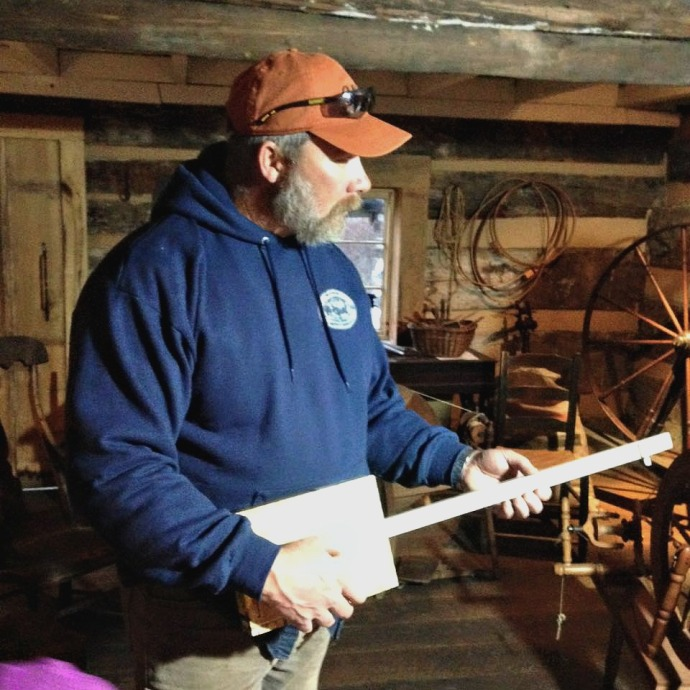 Tom playing a cigar box banjo at Fort New Salem