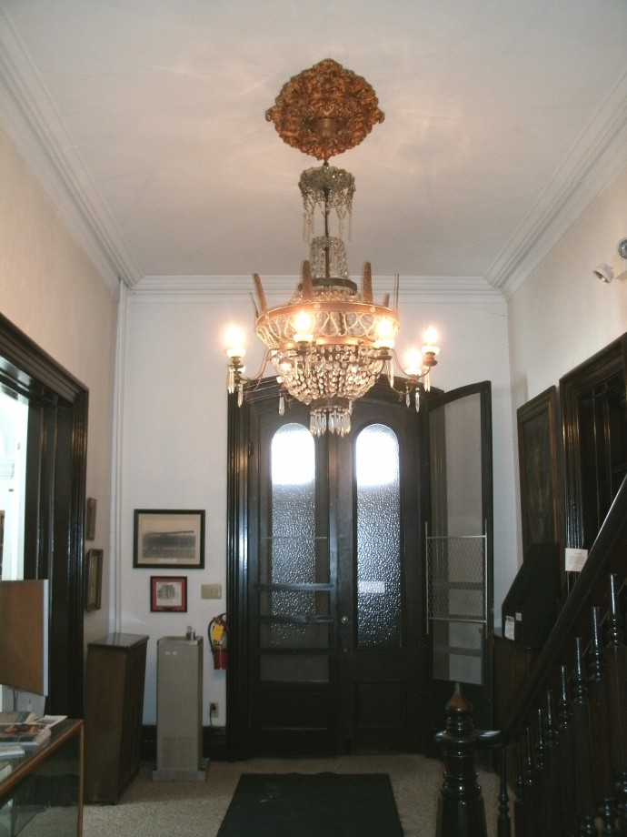 Main hall with a view of the front doors and Chandelier