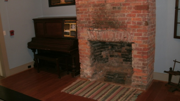 Fireplace and upright piano in dining area in Crawford house, Beverly Heritage Center.