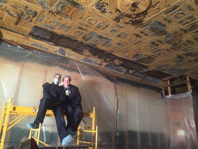 Hands on crew members inside the Sunshine building doing restoration work to the punched tin ceiling