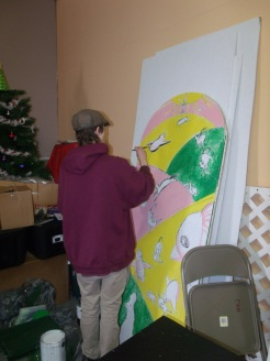 Patrick a AmeriCorps Volunteer painting a window mural for the Golden Rule