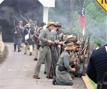 Conferate troops push Union troops from the road onto the grass field below